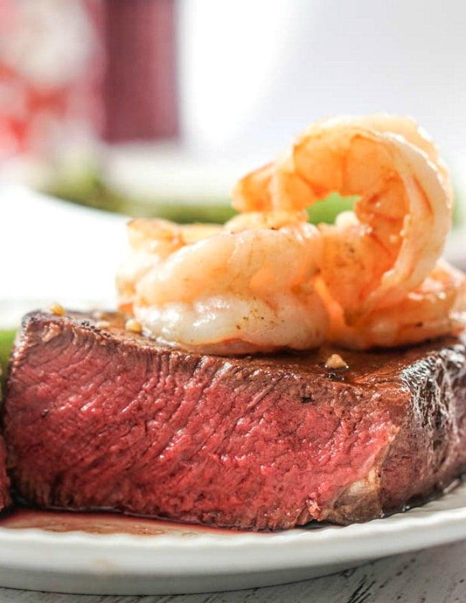Closeup of cut filet medium rare with shrimp on top.