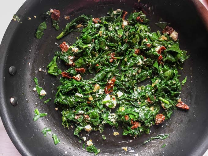 Photo of a pan with spinach, sun dried tomatoes and goat cheese.