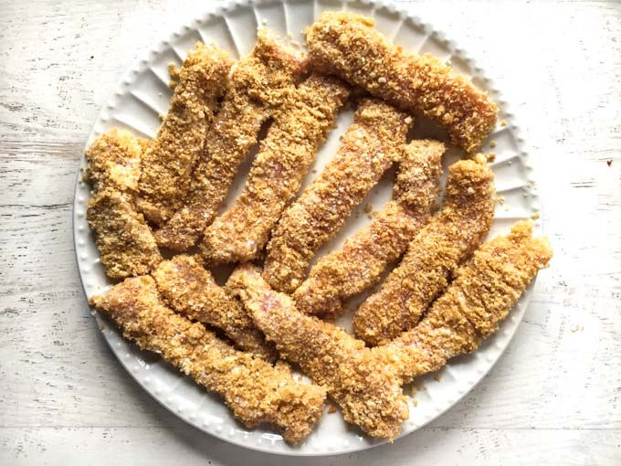 A white plate with breaded pork fries before frying.