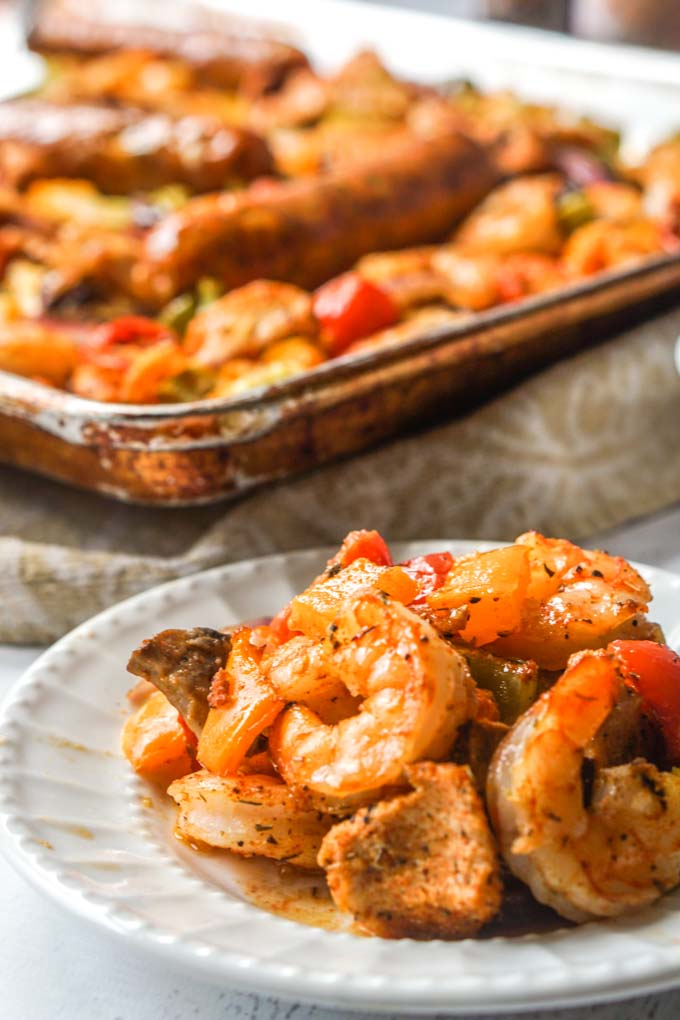 Long photo of small whittle plate with cajun shrimp and vegetables with sheet pan in the background.