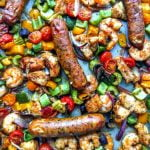 Long photo of a sheet pan with cajun shrimp, chicken and sausages with text overlay.