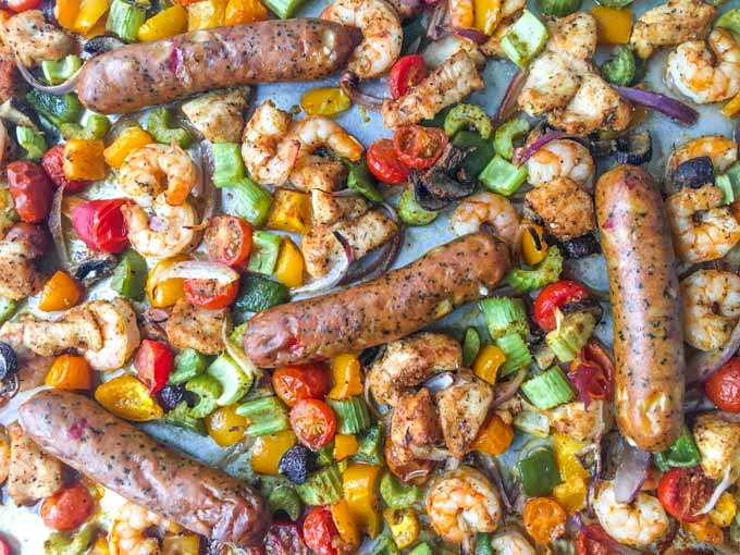 Closeup of sheet pan full of cajun chicken, shrimp, sausage and vegetables.
