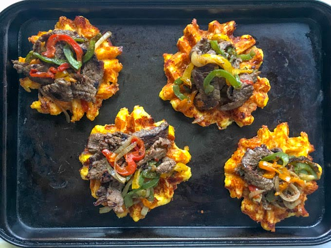 Cheese waffles on a cookie sheet topped with cheesesteak