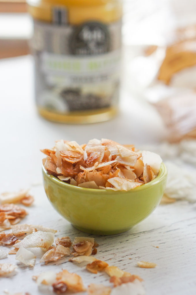Long photo of a small green bowl of toasted coconut chips and a bottle of ghee in the background.