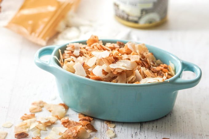 Photo of coconut chips in a blue bowl.
