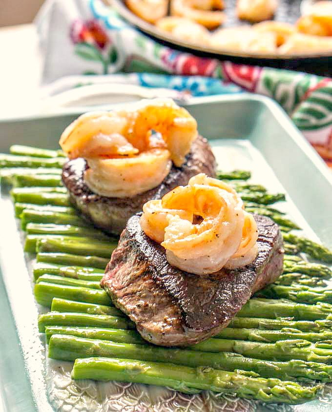 Two filets on a bed of asparagus with shrimp on top with text overlay.