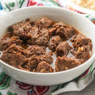 A white bowl with chunks of the Middle Eastern spiced pot roast.