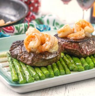 Photo of steaks on asparagus with shrimp pan in back.