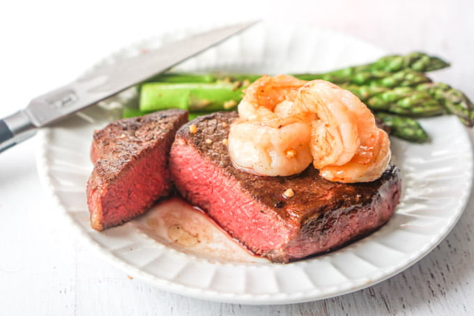 Closeup of cut steak with shrimp and asparagus.