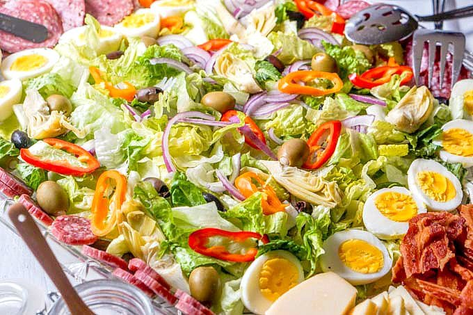 Closeup photo of salad on platter with lots of colorful vegetables.