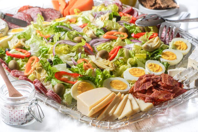 Large platter of salad, cheese and meats with a salt container and wooden spoon.