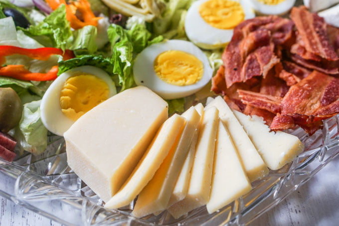 Close up of salad platter showing aged havarti, eggs and bacon.