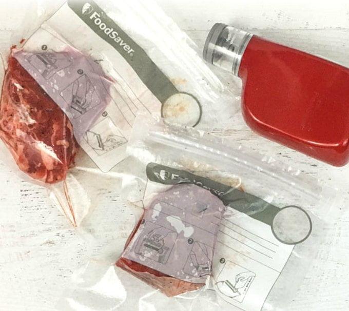 Aerial view of vacuum sealer and vacuum packs of steaks.