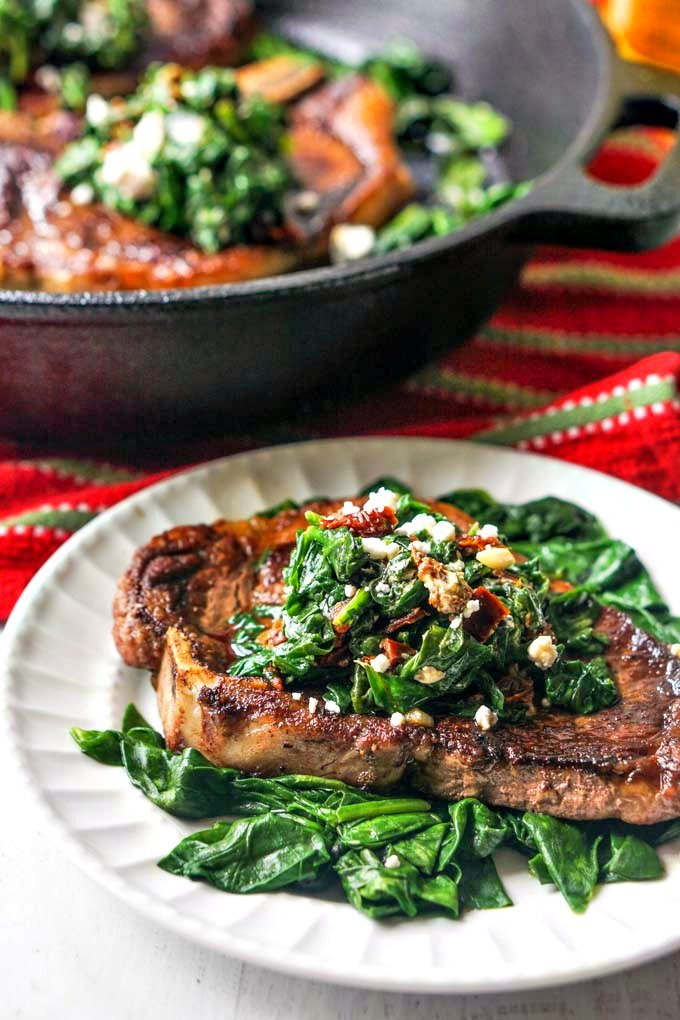 Photo of closeup of steak on white plate and spinach mixture with pan in background.