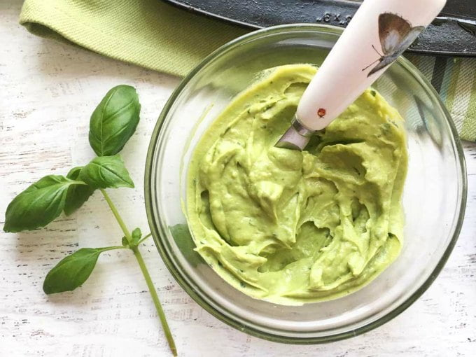 a bowl of basil avocado spread and sprig of basil