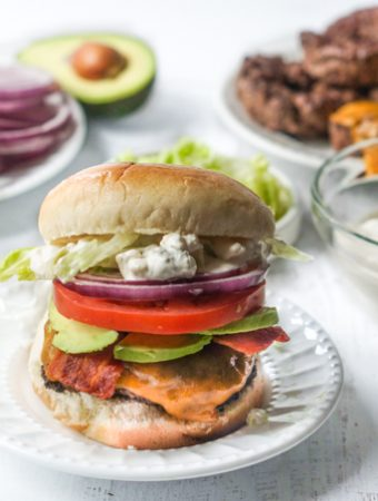 Photo of a burger with lots of toppings and ingredients in background.