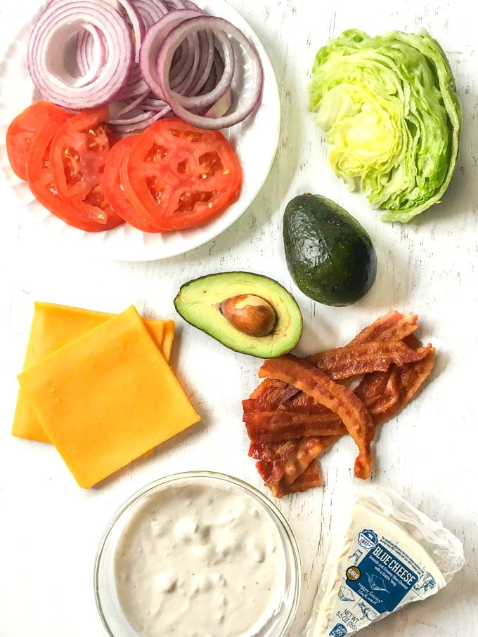 Long photo of burger toppings: bacon, cheese, avocado, blue cheese dressing, salad.