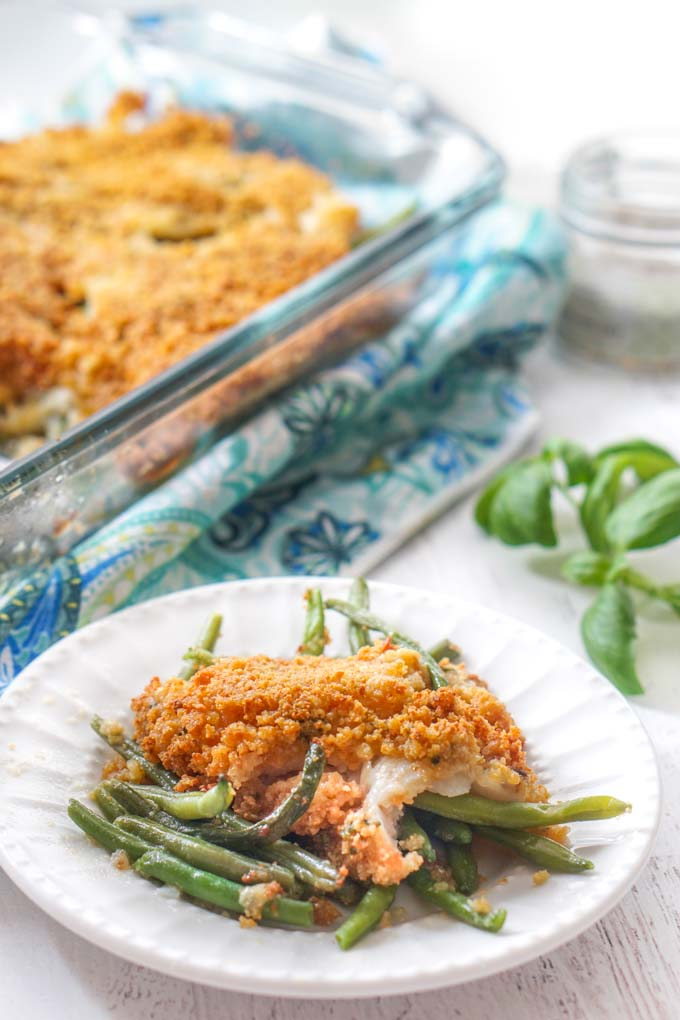 white plate with baked fish and green beans with baking dish in background