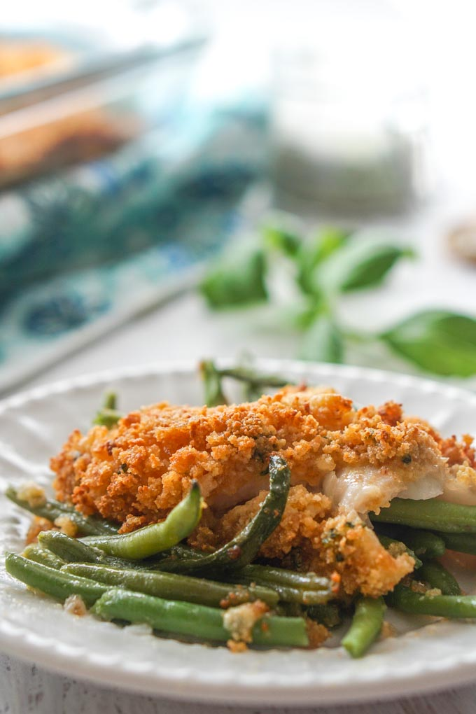 Close up of white plate with green beans and baked fish.