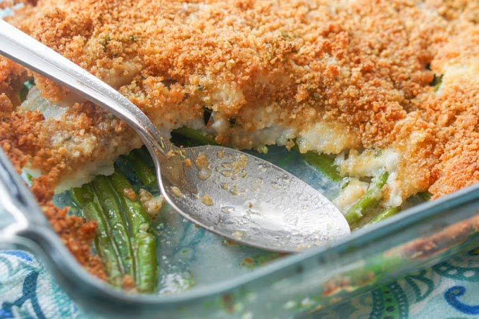 Baked Fish in a casserole dish with a spoon and helping gone