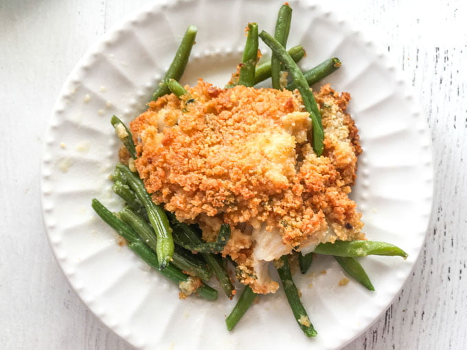 white plate with baked fish on a bed of green beans