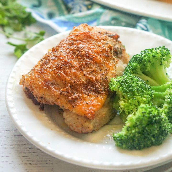 white plate with rotisserie chicken thigh and broccoli