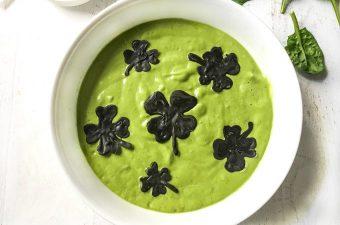 Photo of white bowl full of green smoothie and chocolate shamrocks.