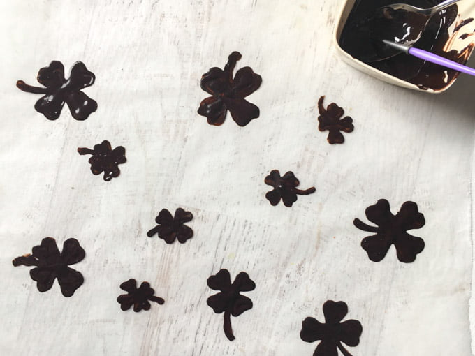 Photo of chocolate shamrocks on parchment paper.