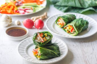 white plates with shrimp spring rolls with vegetables in the background