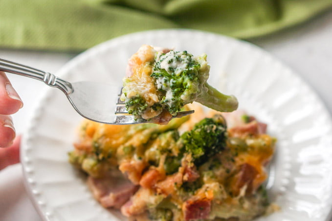 close up of a fork with ham and. broccoli casserole bite