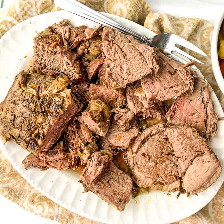 white platter with slice leg of lamb made in the instant pot with silver fork
