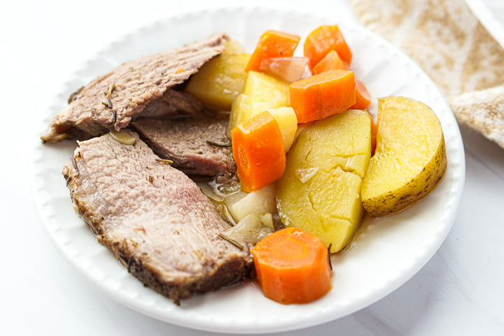 white plate with a serving of sliced roasted lamb and cooked carrots, potatoes and onions