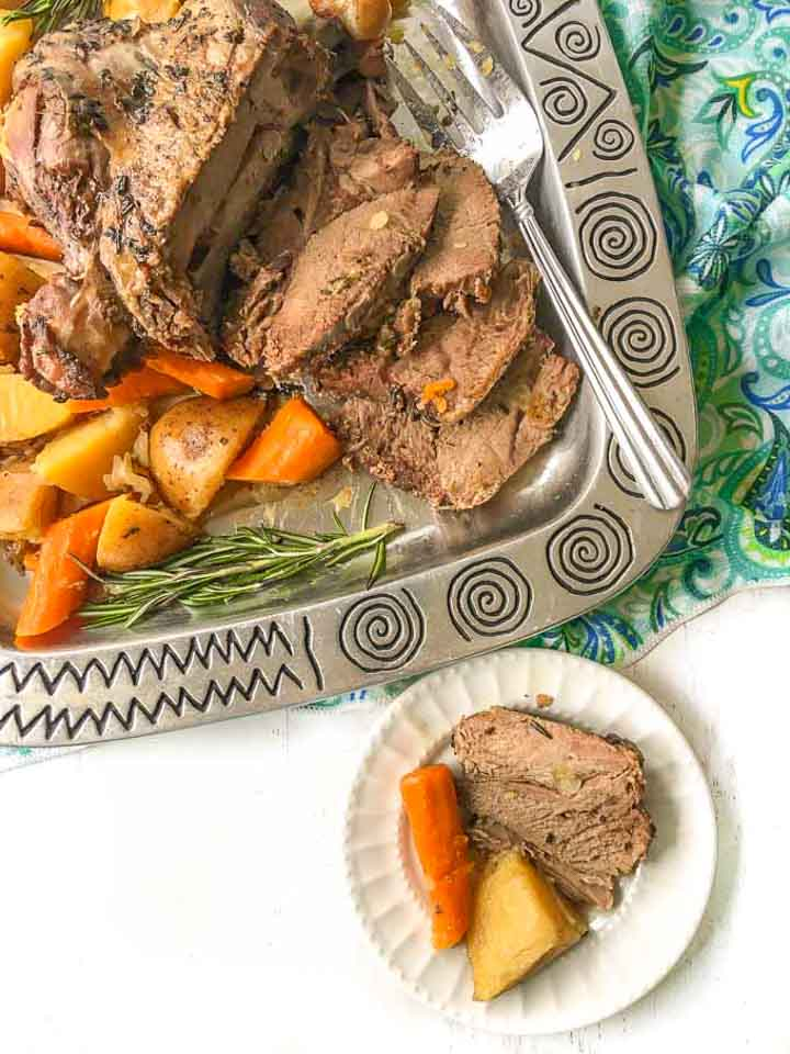 platter with leg of lamb and white dish with potato, carrot and piece of lamb