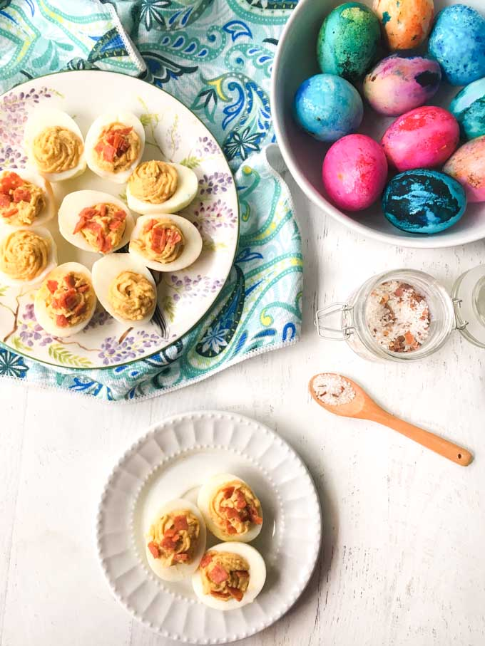 plate of deviled eggs and a bowl of Easter eggs and jar of salt