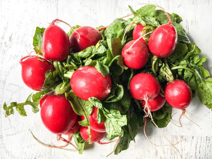 a bunch of fresh, raw radishes and greens