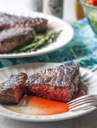 white plate with juicy red steak with platter of steaks in background