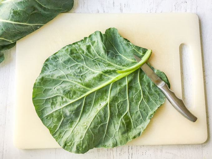 large raw collard greens leaf with knife on cutting board