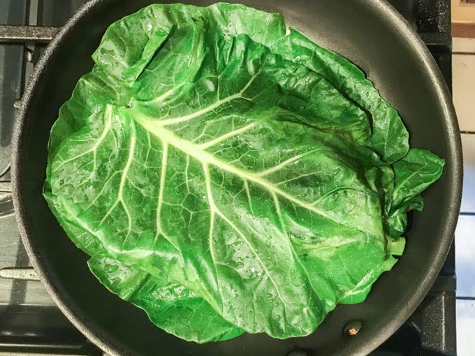 large collard greens leaf in saute pan
