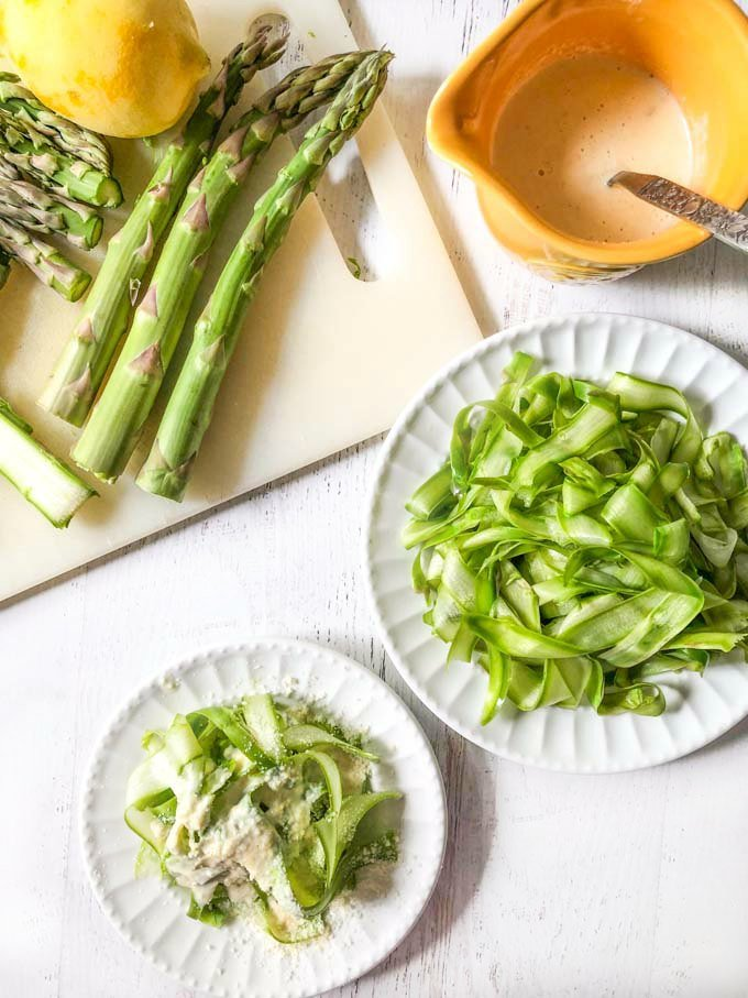 white plates with asparagus noodles and cutting board with spears