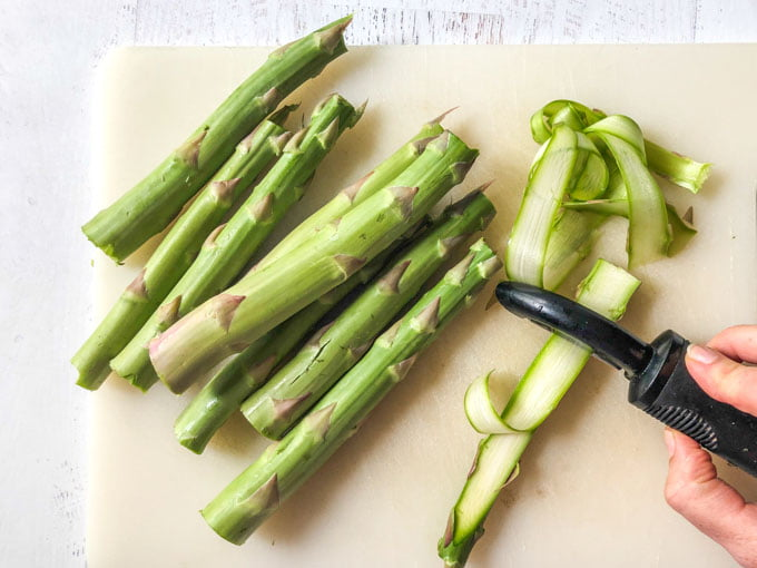 asparagus on cutting boar and peeler making noodles
