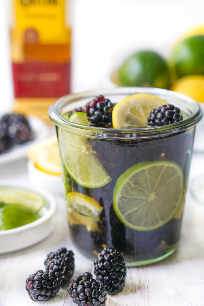 jar of blackberries, limes and tequila with bottle of tequila in background