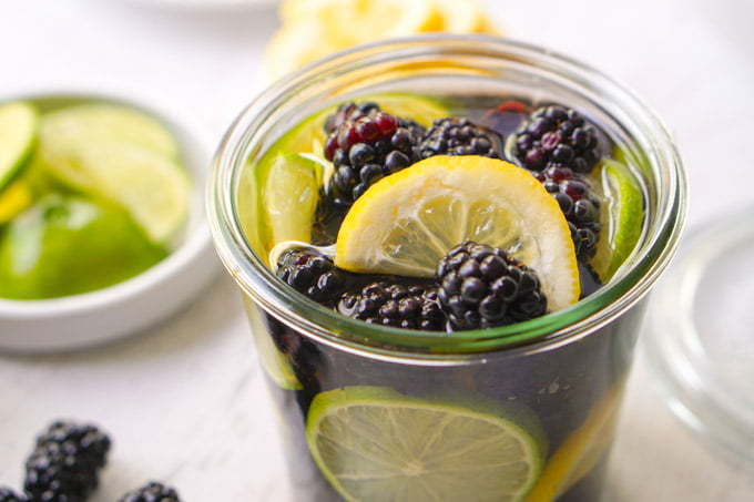 closeup of jar of blackberries, lemons and limes with tequila infusion