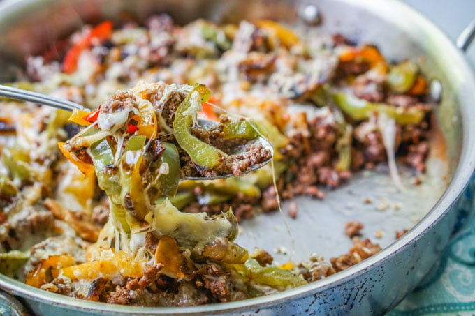 A skillet of cheesesteak with ground beef and a big spoon scooping it up
