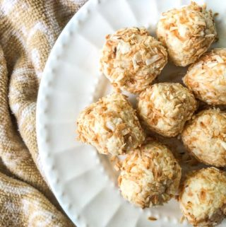 closeup of coconut protein balls on white plate with beige towel