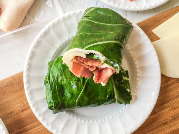 collard green turkey club wrap on white plate
