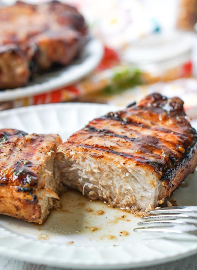 closeup of a white plate with a cut grilled glazed pork chop