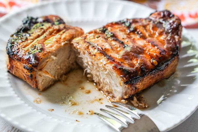 white plate with a cut grilled glazed pork chop