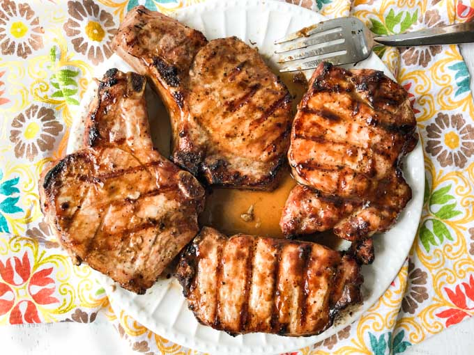 white plate with a cut grilled cooked pork chop with a colorful tea towel