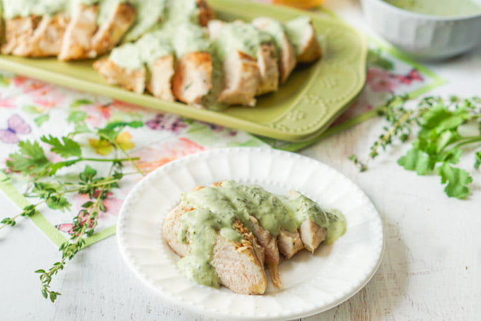 green platter and white plate with sliced sous vide chicken breast and creamy herbs sauce.