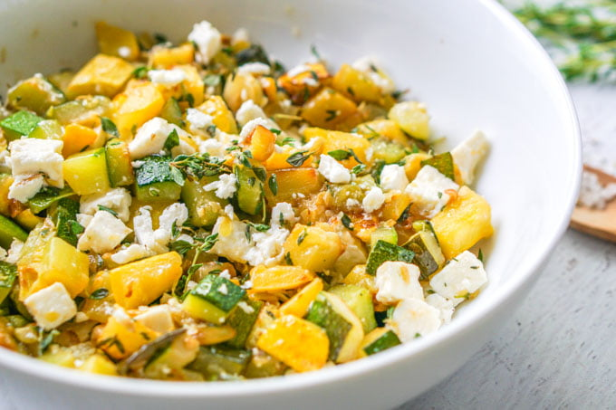 big white bowl of zucchini side dish with feta cheese and fresh thyme
